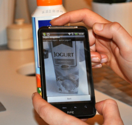 Object recognition application runs on a HTC Smartphone. The application software successfully recognizes the object (apricot yogurt) and displays the reference image.